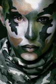 Beautiful young fashion woman with military style clothing and face paint make-up, khaki colors, halloween celebration swag poster