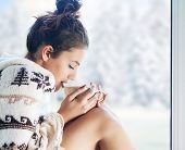 Young beautiful brunette woman drinking cup of coffee wearing knitted nordic print poncho sitting home by the window. Blurred winter snow tree background.  poster