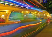 High-speed vehicles bright light trails on urban roads under overpass at night poster