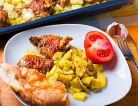 Plate Of Chicken And Potatoes Baked On A Grill