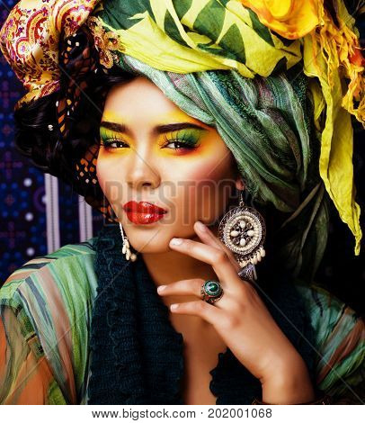 beauty bright woman with creative make up, many shawls on head like cubian, ethno look