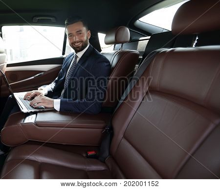 smiling businessman sitting in the back seat of a prestigious ca