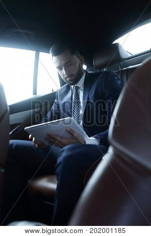 businessman with a digital tablet sitting in the back seat of a