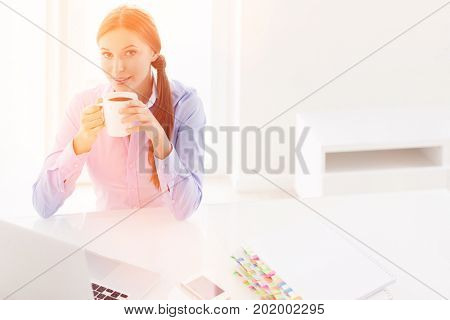 Beautiful woman drinking coffee at her desk