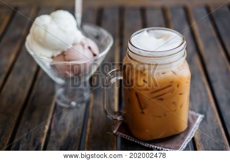Iced Coffee with Ice Creams on wooden table, selective focus on Coffee Cup, Summer Dessert