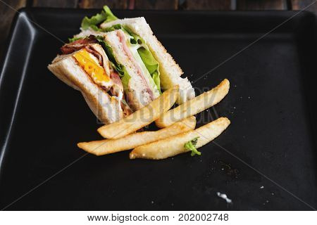 Leftover toasted club sandwich with french fries on black dish