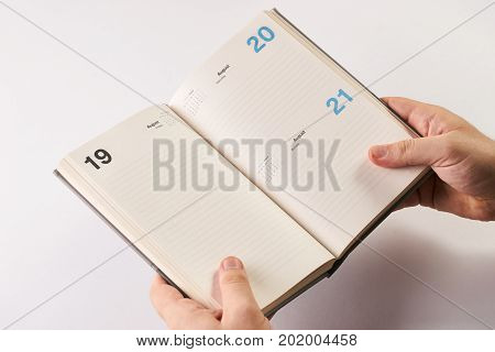 Hand Holding Notebook Over White Background.