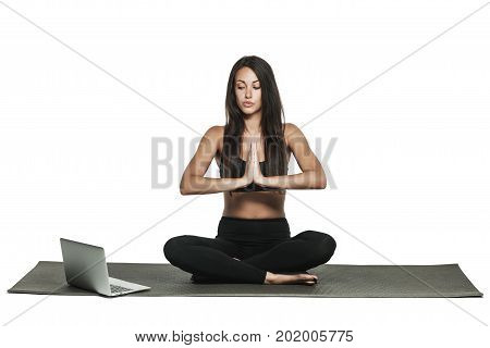Young woman doing yoga and glancing at her laptop. Busy woman combines work and fitness. Isolated on white.
