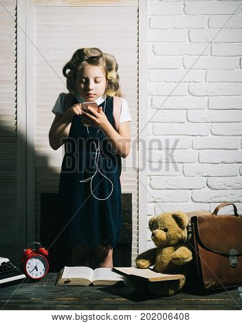 Child with briefcase and alarm clock. Small girl with curler in hair with headset and phone. Kid choose career and listen music. Education and childhood. Little baby secretary with bear and book.