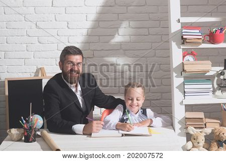 Schoolgirl And Dad With Happy Faces Hold Write In Notebook