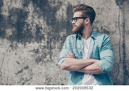 Side View Portrait Of Handsome Brutal Bearded Guy Dressed In Casual Clothes Standing With Crossed Ar