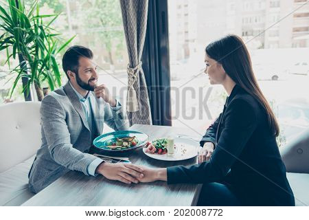 Love Is In The Air. Side Profile View Of Two Young Cute Lovers, Stting In A Restaurant`s Terrace In