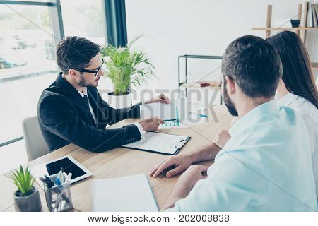 Rear View Of Couple Sitting In The Brunet`s Smart Lawyer`s Work Station,  Discussing The Possibility