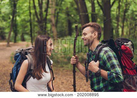 Cute Excited Lovers Are Hiking In A Spring Forest, Talking And Enjoying, Wearing Comfortable Outfits