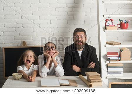 Girls and bearded man sit at desk with books. Teacher and schoolgirls on classroom background. Kid older sister and their tutor with happy and dreamy faces. Home schooling and back to school concept