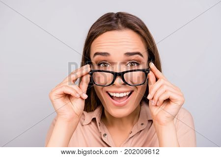 Close Up Of An Amazed Brunette Young Woman In Beige Formal Shirt And Glasses, Holding Them, She Is S