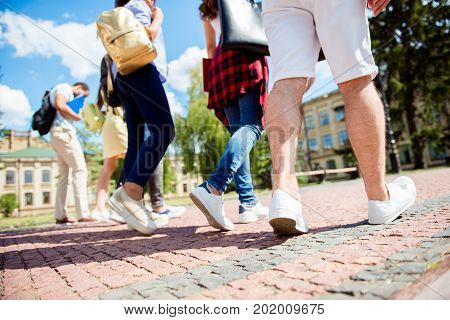 Low Angle Rear View Shot Of Six Student`s Feet, They Are Walking Outside In The Park Near Te College
