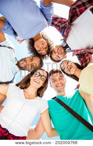 Low Angle Shot Of Six International Students With Toothy Smiles, Posing And Bonding, On A Sky Backgr