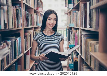 Young attractive clever successful asian female student is holding big thesaurus in hard bookcase wearing casual striped t shirt behind her are book shelves of campus library