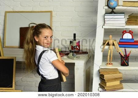 Schoolgirl Holds Textbook On Light Brick Wall Classroom Background
