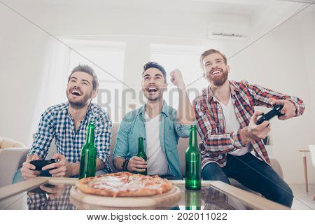Yes! Team of winners! Bachelor men`s life. Low angle of three happy joyful men sitting on sofa and playing video games with beer and pizza smiling gesturing enjoying themselves