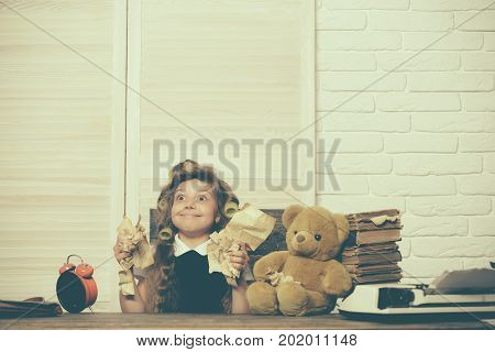 Small girl with curler in hair. Kid choose career. Little baby secretary with bear and book. Child with alarm clock. Education and childhood.