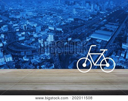 Bicycle flat icon on wooden table over modern city tower street and expressway Healthy lifestyle concept