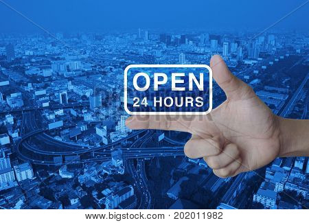 Open 24 hours icon on finger over modern city tower street and expressway Business full time service concept