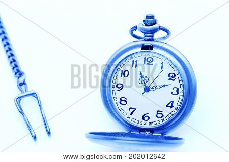 antique pocket watch with chain on blue background