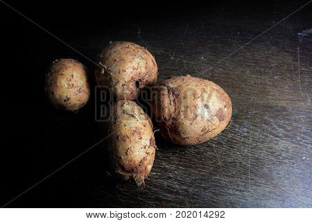 Group Of Wild Yam On Wooden Table With Dark Light Background