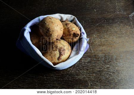 Wild Yam In The Bag On Wooden Table With Dark Light Background