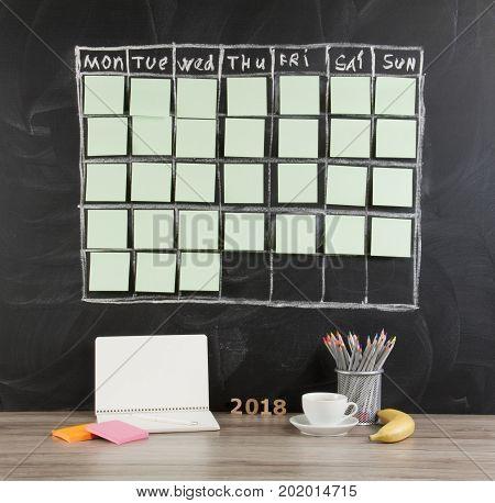 Grid timetable schedule on black chalkboard background.