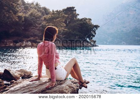 A Woman Is Sitting At Ease By The Sea .young Girl Enjoying Blue Mediterranean View Alone Travel Life