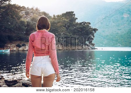 A Woman Is Standing  At Ease By The Sea .young Girl Enjoying Blue Mediterranean View Alone Travel Li