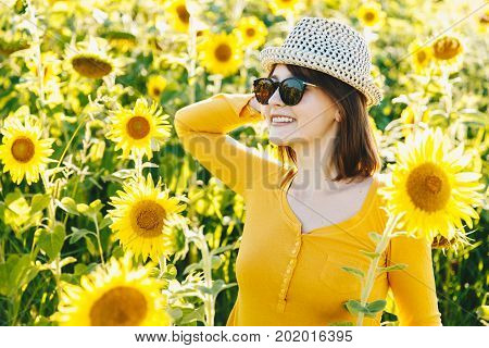 Summer Gir On Hat And Sunglasses. Beautiful Cheerful Young Woman With Sunflower Enjoying Nature And