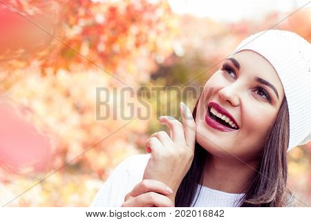 Beautiful Young Woman In A White Knitted Cap Walks In Autumn Park. Red Trees. Leaves. Warm Autumn. A