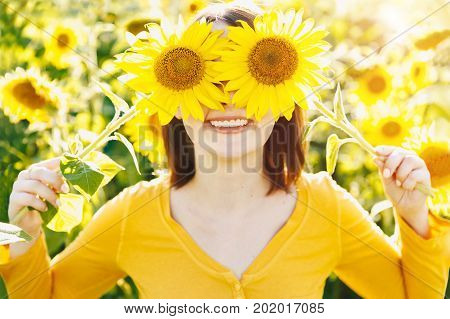 Summer Girl. Beautiful Cheerful Young Woman  With Sunflower Enjoying Nature And Laughing On Summer S