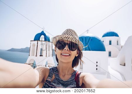Pretty Cheerful Young Woman Holding Smart Phone And Take A Self Portrait On Greek Street. Tourism, P