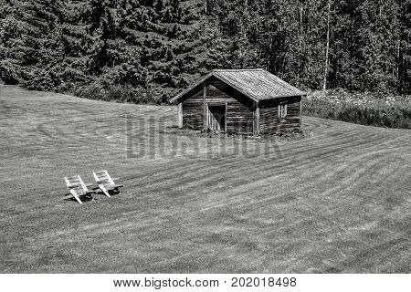Wooden shed and chairs in Finland for relaxing time black and white
