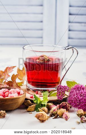 Red herbal tea with herbs and flowers in a glass tea pot. Copy space