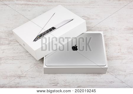 BURGAS, BULGARIA - AUGUST 29, 2017: MacBook Pro Retina Display with Touch bar and a Touch ID sensor integrated into the Power button, made by Apple Inc. on white wooden background.