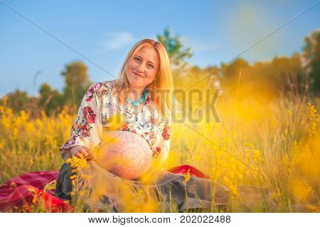 9 months pregnant woman with mehandi pattern ornament belly sitting in yellow grass and smiling on sunset lights. Waiting for baby. Pregnancy concept
