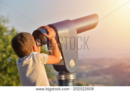 Little boy looking into tourist telescope eyepiece. Travel tourist destination landscape magnification