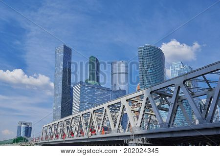 View on Moscow City business center skyscrapers office buildings, luxury apartments and metal railway bridge with red train. Moscow city skyscrapers panorama. Modern european russian architecture