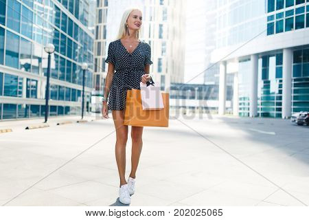 Full-length photo of young model in dress with purchases on city street near buildings