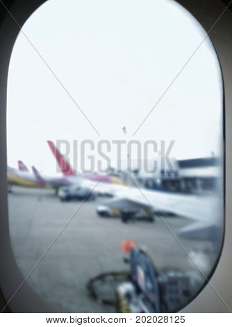 Blur window view of activities outside a plane at an airport; aircraft refuelling operation; airplanes parking at terminal gates waiting for boarding - Top copy space for adding text