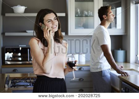 Beautiful woman in kitchen on call smiling
