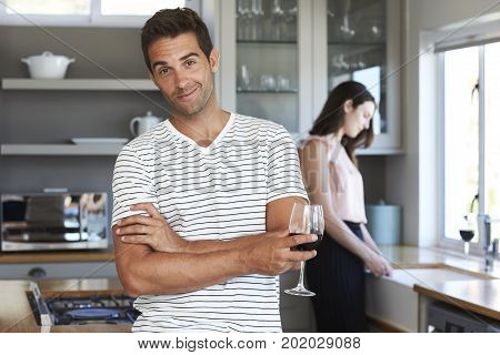 Portrait of smiling guy in kitchen with wine