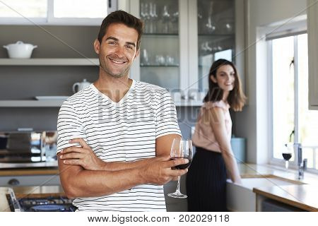 Happy guy in striped t-shirt holding wine in kitchen