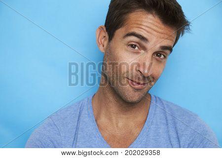 Handsome guy raising eyebrow in blue portrait